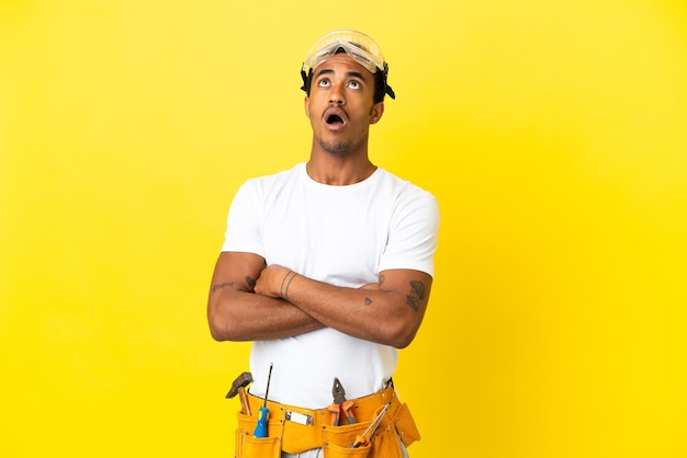 Afro-amerikaanse elektricien man over geïsoleerde gele muur opzoeken en met verbaasde uitdrukking
