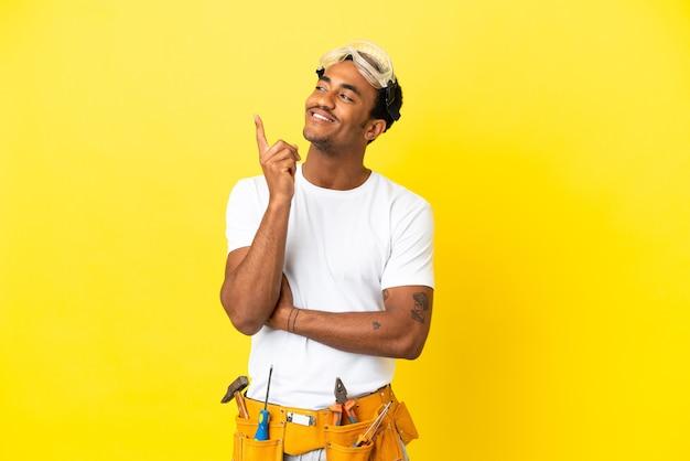 Afro-amerikaanse elektricien man over geïsoleerde gele muur wijzend op een geweldig idee
