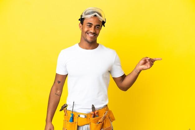 Afro-amerikaanse elektricien man over geïsoleerde gele muur wijzende vinger naar de zijkant