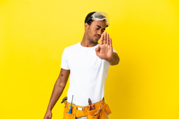 Afro-amerikaanse elektricienman over geïsoleerde gele muur die een stopgebaar maakt en teleurgesteld is?