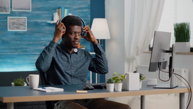 Afro-amerikaanse etniciteit freelancer zet koptelefoon op thuiswerken externe werknemer computer...