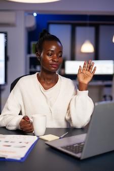 Afro-amerikaanse executive manager groet zakelijke collega op afstand