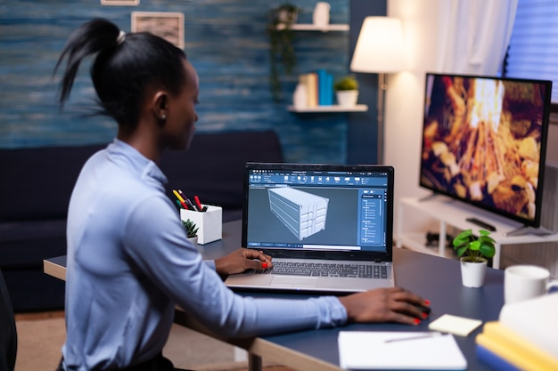 Afro-amerikaanse externe vrouw architect bezig met moderne cad-programma overuren. industriële zwarte vrouwelijke ingenieur die prototype-idee bestudeert op een personal computer die software op het apparaatscherm toont