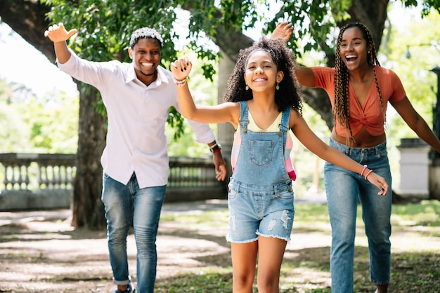 Afro-amerikaanse familie die plezier heeft en samen geniet van een dag buiten in het park.