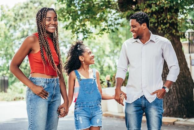 Afro-amerikaanse familie die samen buiten op straat wandelt