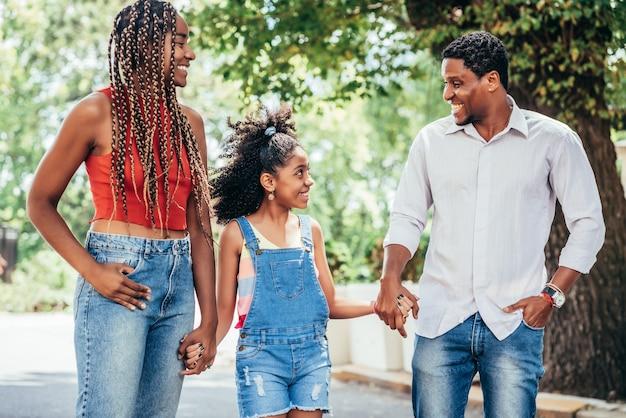Afro-amerikaanse familie genieten van een wandeling samen buiten op straat