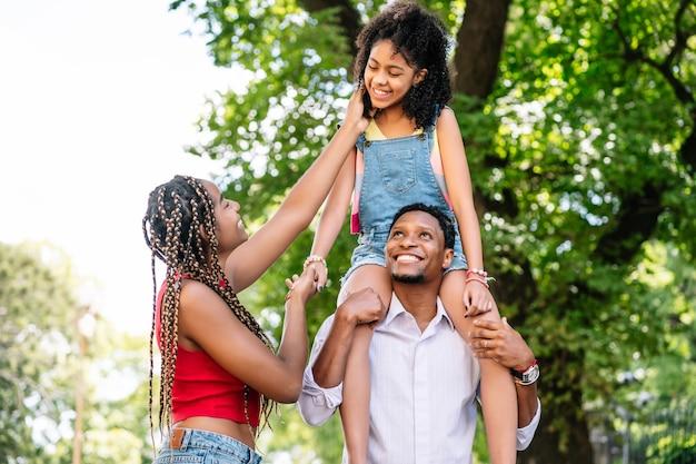 Afro-amerikaanse familie met plezier en goede tijd samen doorbrengen tijdens het wandelen buiten op straat.