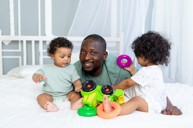 Afro-amerikaanse familievader met kinderen, baby's spelen en verzamelen een kleurrijke piramide thuis op het bed, gelukkig gezin