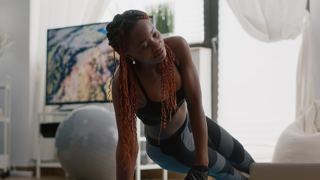 Afro-amerikaanse fitte vrouw die sportkleding draagt en beenoefeningen doet