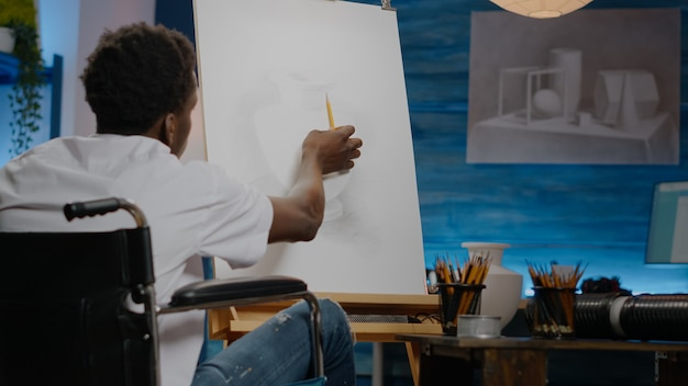 Afro-amerikaanse gehandicapte jonge kunstenaar die vaas op canvas trekt