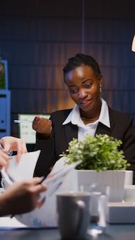 Afro-amerikaanse gerichte ondernemer brainstormt bedrijfsstrategie die 's avonds in de vergaderruimte werkt. diverse multi-etnische collega's die managementpresentatie papierwerk analyseren
