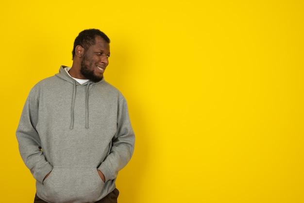 Afro-amerikaanse glimlachende man die naar links kijkt, staat over de gele muur.