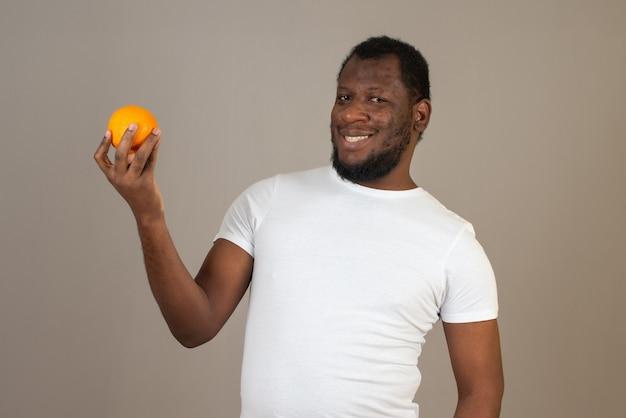 Afro-amerikaanse glimlachende man kijkt naar de mandarijn in zijn hand, staande voor de grijze muur.