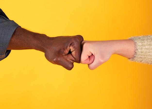 Afro-amerikaanse hand en blanke hand geven vuist hobbels.