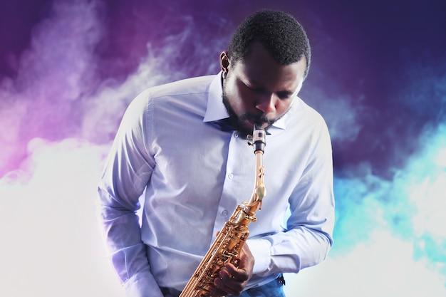 Afro-amerikaanse jazzmuzikant die de saxofoon speelt tegen kleurrijke rokerige