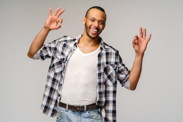 Afro-amerikaanse jonge man draagt casual shirt en ok teken tonen over lichtgrijze achtergrond.