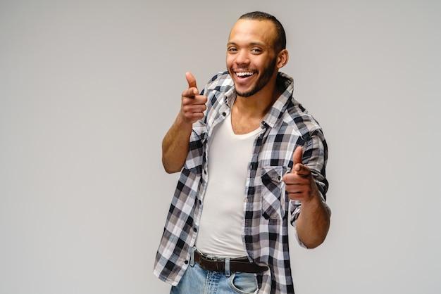 Afro-amerikaanse jonge man dragen casual shirt en duimen opdagen over lichtgrijze achtergrond.
