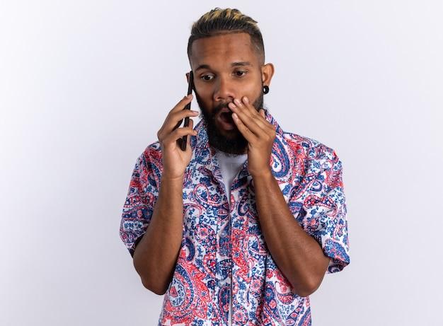 Afro-amerikaanse jonge man in kleurrijk shirt die verbaasd en geschokt kijkt terwijl hij op een mobiele telefoon praat die over wit staat