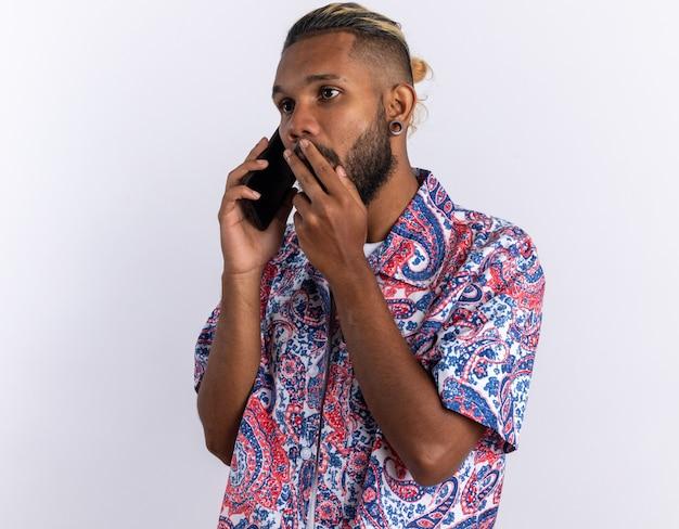 Afro-amerikaanse jonge man in kleurrijk shirt die verbaasd kijkt terwijl hij op een mobiele telefoon praat die over wit staat