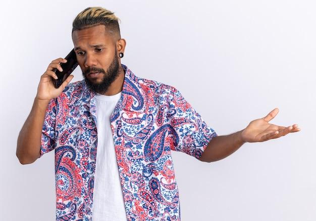 Afro-amerikaanse jonge man in kleurrijk shirt die verward kijkt terwijl hij op een mobiele telefoon praat die over een witte achtergrond staat