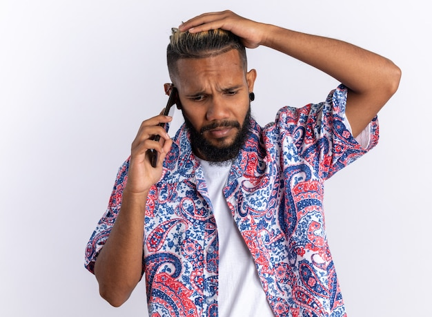 Afro-amerikaanse jonge man in kleurrijk shirt die verward kijkt terwijl hij op een mobiele telefoon praat die over wit staat