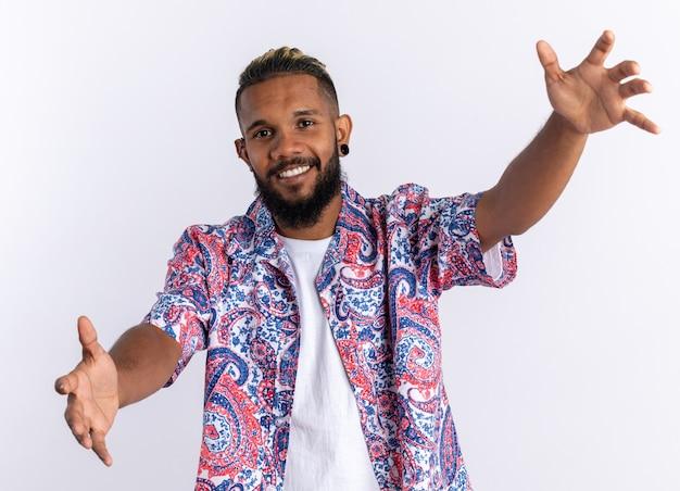 Afro-amerikaanse jonge man in kleurrijk shirt kijken camera blij en vrolijk