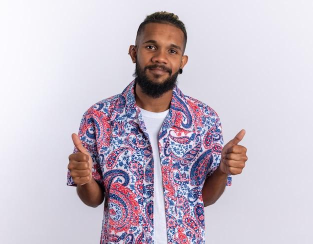 Afro-amerikaanse jonge man in kleurrijk shirt kijken camera glimlachend vrolijk duimen opdagen