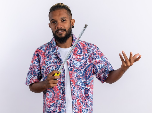 Afro-amerikaanse jonge man in kleurrijk shirt met meetlint kijkend naar camera glimlachend met blij gezicht staande op witte achtergrond