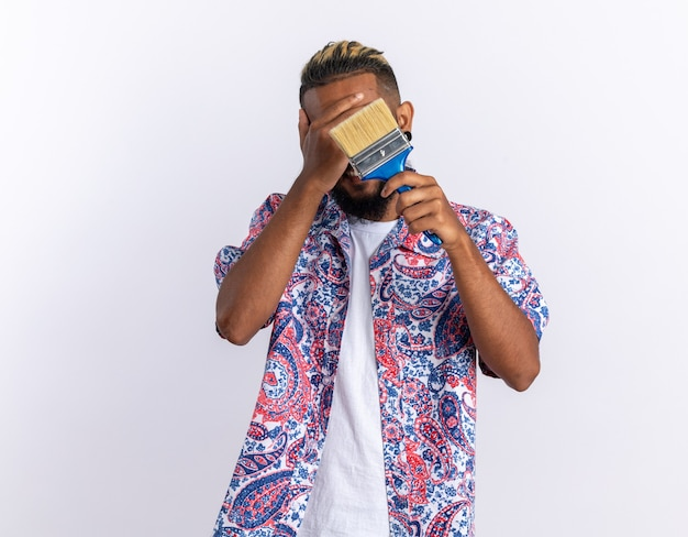 Afro-amerikaanse jonge man in kleurrijk shirt met verfborstel die ogen bedekt met de hand die op een witte achtergrond staat