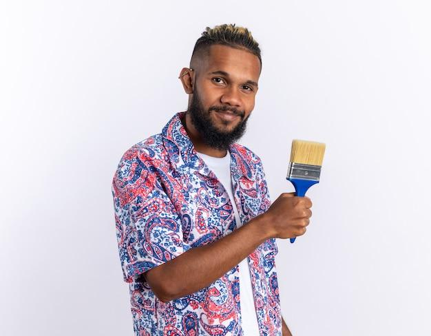 Afro-amerikaanse jonge man in kleurrijk shirt met verfborstel kijkend naar camera glimlachend