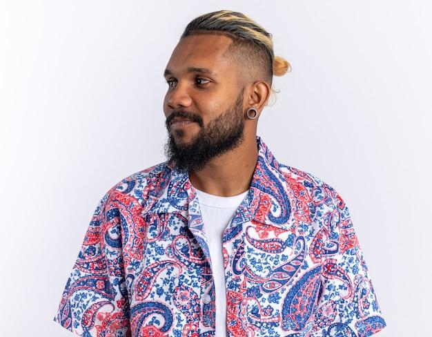 Afro-amerikaanse jonge man in kleurrijk shirt opzij kijkend glimlachend vrolijk staande over witte achtergrond
