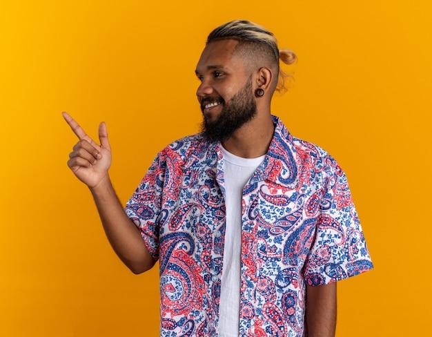 Afro-amerikaanse jonge man in kleurrijk shirt opzij kijkend glimlachend vrolijk wijzend met wijsvinger naar de zijkant over oranje achtergrond