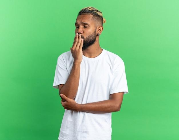 Afro-amerikaanse jonge man in wit t-shirt blaast een kus gelukkig en zelfverzekerd over groene achtergrond