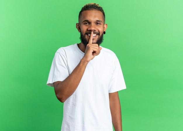 Afro-amerikaanse jonge man in wit t-shirt kijken camera glimlachend vrolijk stilte gebaar maken met vinger op lippen permanent over groene achtergrond