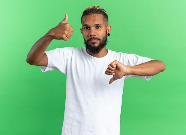 Afro-amerikaanse jonge man in wit t-shirt kijken camera verward duimen opdagen