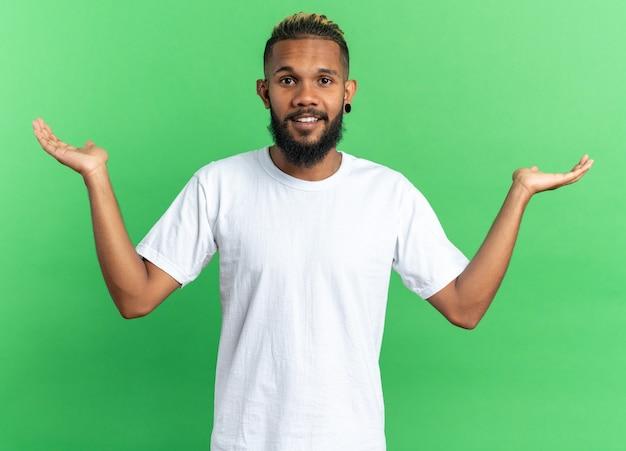 Afro-amerikaanse jonge man in wit t-shirt kijkend naar camera glimlachend vrolijk spreidende armen naar de zijkanten staande over groene achtergrond