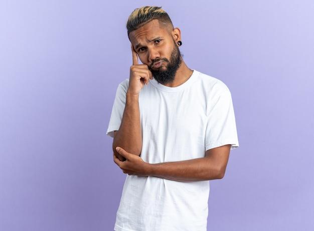 Afro-amerikaanse jonge man in wit t-shirt kijkend naar camera verbaasd over blauwe achtergrond