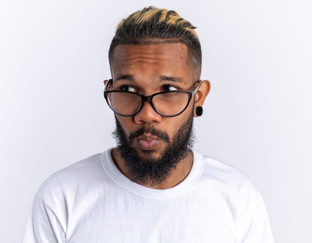 Afro-amerikaanse jonge man in wit t-shirt met bril opzij kijkend verbaasd over wit staan