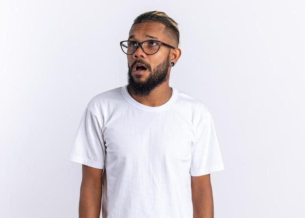 Afro-amerikaanse jonge man in wit t-shirt met bril opzij kijkend verward en verrast