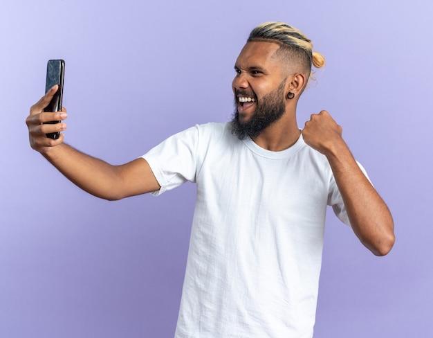 Afro-amerikaanse jonge man in wit t-shirt met smartphone balde vuist gelukkig