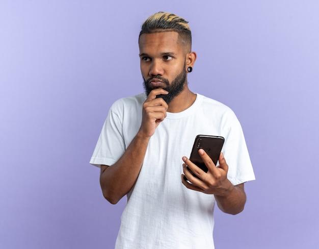 Afro-amerikaanse jonge man in wit t-shirt met smartphone opzij kijkend verbaasd over blauwe achtergrond
