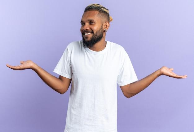 Afro-amerikaanse jonge man in wit t-shirt opzij kijkend glimlachend vrolijk spreidende armen naar de zijkanten staande over blauwe achtergrond
