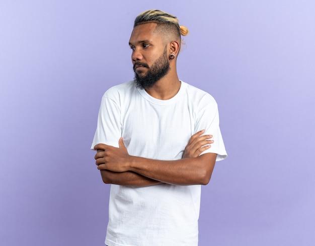 Afro-amerikaanse jonge man in wit t-shirt opzij kijkend met een serieus gezicht