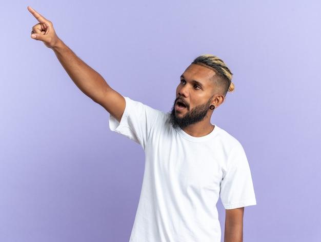 Afro-amerikaanse jonge man in wit t-shirt opzij kijkend verward wijzend met wijsvinger naar iets dat over blauwe achtergrond staat