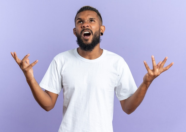 Afro-amerikaanse jonge man in wit t-shirt schreeuwen gefrustreerd met opgeheven armen over blauw