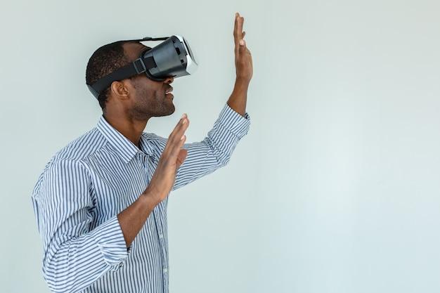 Afro-amerikaanse jonge man met vr virtual reality headset over witte muur