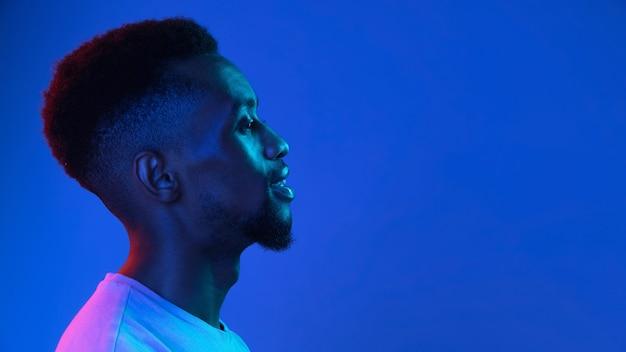 Afro-amerikaanse jonge mans portret op donkere studio muur in neon zijaanzicht