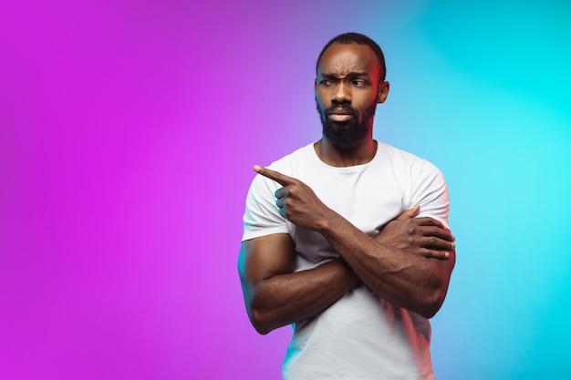 Afro-amerikaanse jonge mans portret op gradiënt studio achtergrond in neon