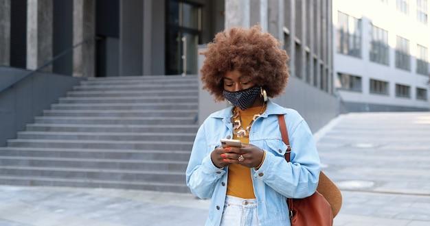 Afro-amerikaanse jonge stijlvolle mooie hipster vrouw met krullend haar pruik en in masker wandelen op stedelijke straat en het gebruik van smartphone. mooie vrouw buiten in stad sms-bericht op mobiele telefoon.
