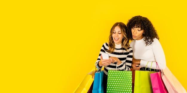 Afro-amerikaanse jonge verrast vrouw met wow gezicht op zoek smartphone van haar vriend met verschillende gekleurde papieren zakken. twee shopaholic meisjes met plezier met online winkelen geïsoleerd op gele kopie ruimte